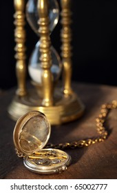 Blurred sandglass on the background of an antique pocket watch