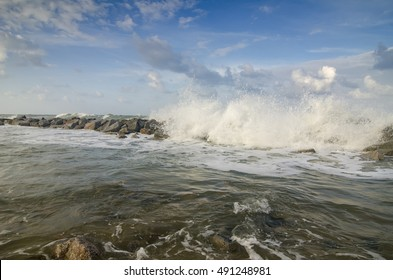 blurred and selective focus image of wave hitting breakwater on the beach over cloudy and blue sky background
