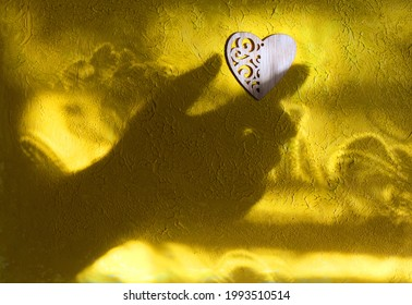 Blurred shadow of female hand and two wooden heart on rough yellow wall background. Sunlight and  crossed lines shadows, Minimal aesthetics