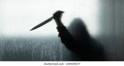 Blurred shadow of hand holding big sharp knife behind frosted glass in the bathroom background.Robber,murderer or killer with knife.concept of scary crime scene of horror or thriller movies,Halloween