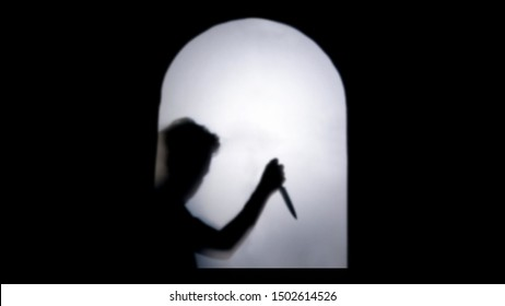 Blurred shadow of hand holding big sharp knife behind white mirror background. killer with knife.concept of scary crime scene of horror or thriller movies,Halloween theme