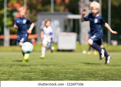 Blurred shot of kids playing outdoors soccer on a sunny day.