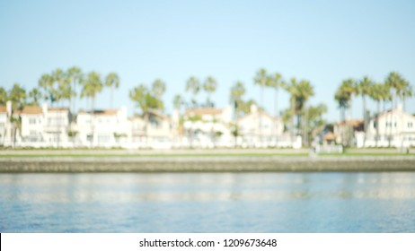 Blurred shot of oceanfront homes and palm trees under a sunny sky