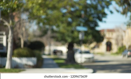 Blurred shot of a typical street sign and trees in suburban neighborhood