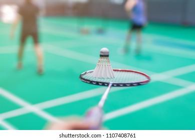 blurred shuttercock on badminton racket with blurred background badminton player, indoor court.