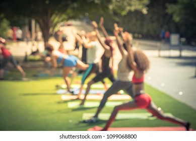 Blurred side view diverse group of active people participating free public Yoga class at urban park. Outdoor Yoga training class on grass at summer day in Dallas, Texas, USA, healthy lifestyle concept