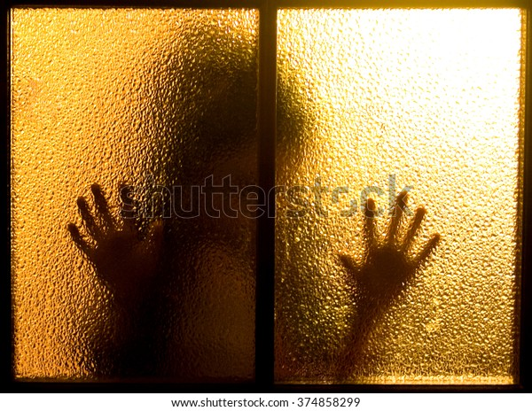 Blurred silhouette behind a window or glass door (symbolizing sadness, loneliness, horror or fear)
