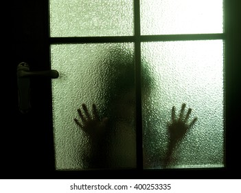Blurred silhouette of a child behind a glass door in the darkness (symbolizing sadness, loneliness, horror or fear)