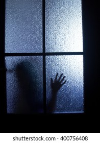 Blurred silhouette of a child behind a glass door in the darkness (in blue tones)