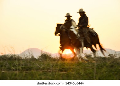 Blurred silhouette of a cowboy riding a horse