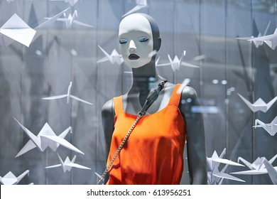 Blurred silhouette of a dressed mannequin in clothes in a showcase of a fashionable shop in a modern shopping center. Bright abstract background ideal for any design