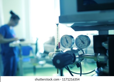 Blurred silhouette of a female medical worker on the background of gas equipment, unfocused background.