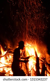 blurred silhouette of a prowling man in profile against a big bonfire with sparks, arson concept
