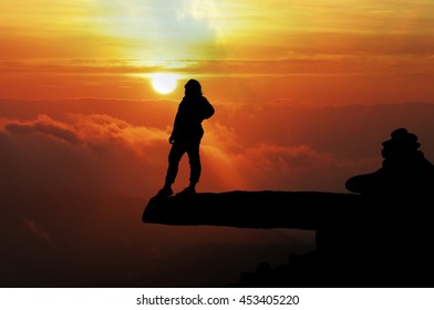 Blurred of silhouette of woman success on top mountain at sunset