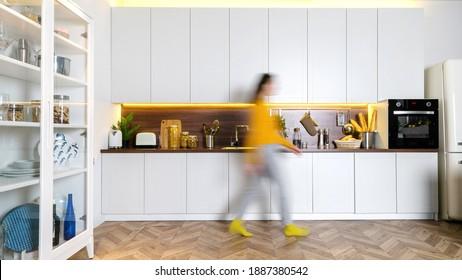 Unscharfe Silhouette junger Frauen, die zu Hause spazieren. Panoramasicht auf das moderne Interieur mit weißen Küchenschränken, Holztheke, Elektroofen