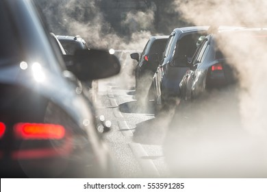 Blurred silhouettes of cars surrounded by steam from the exhaust pipes. Traffic jam
