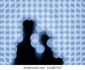 Blurred silhouettes on background lights