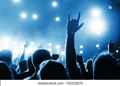 blurred Silhouettes of people in a bright in the pop rock concert in front of the stage. Hands with gesture Horns. That rocks. Party in a club