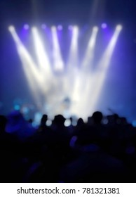 Blurred singer on stage with white and violet light, crowd people in the party, bokeh effect.