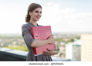 Blurred sky and city on background, attractive brunette caucasian business lady in patterned dress and watch stand on the roof and hold red paper folder, hugs folder, smiling