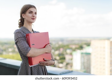 Blurred sky and city on background, attractive brunette caucasian business lady in patterned dress and watch stand on the roof and hold red paper folder, hugs folder
