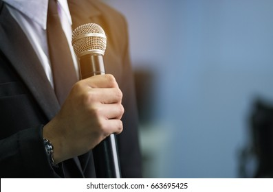 blurred of smart businessman speech, talking with microphone in seminar conference meeting hall, selective focus