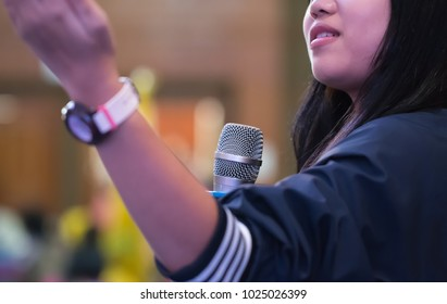blurred of smart businesswoman speech and speaking with microphones in seminar room or talking conference hall light with microphones and keynote. Speech is vocalized form of communication humans.