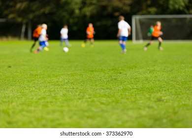 Blurred soccer players playing soccer match on green soccer pitch on sunny summer day
