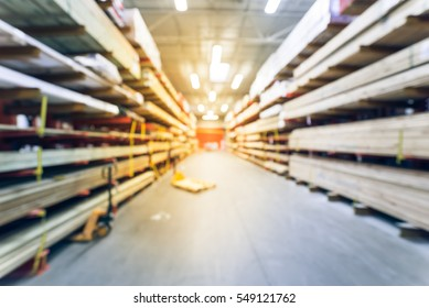 Blurred stack new wooden bar on shelves inside lumber yard of large hardware store in America. Rack of fresh mill/cut wood timber with flatbed cart, manual forklift in warehouse. Industrial background