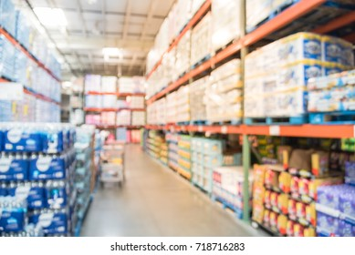 Blurred stack of paper product (napkins, towels) and bottled water from floor to ceiling in large warehouse. Wholesale big box store in USA, shopping cart. Defocused industrial distribution storehouse