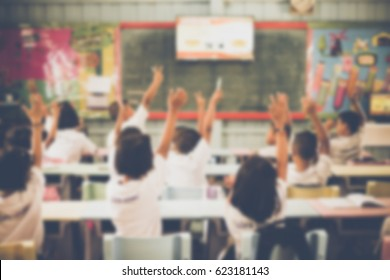 Blurred Student hands up asking a question in class at the elementary school. Education concept.