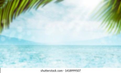 Blurred summer natural marine tropical blue background with palm leaves and sunbeams of light. Sea and sky with white clouds. Copy space, summer vacation concept