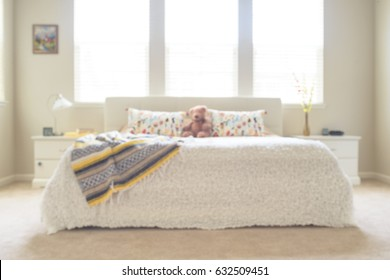 Blurred sunny bedroom in white and yellow colors
