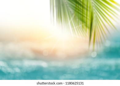 Blurred sunset, sea water bokeh and palm leaf for background. Blurred tropical sea at sunset.