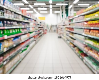 Unscharfer Supermarktgang mit bunten Regalen von Waren. Perspektive Sicht auf abstrakte Supermarkt-Gang mit Kopienraum im Zentrum, kann als Hintergrund oder Einzelhandelskonzept verwenden