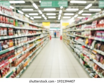Blurred supermarket aisle with colorful shelves of merchandise. Perspective view of abstract supermarket aisle with copy space in center, can use as background or retail concept