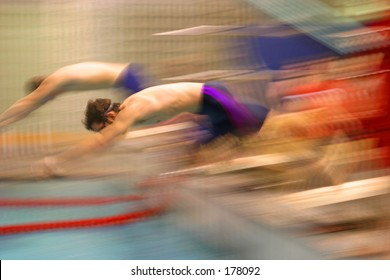 Blurred swimmers diving into a pool.