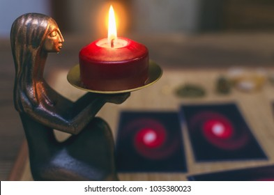 Blurred Tarot cards on the table with burning candle ahead. Future reading concept.