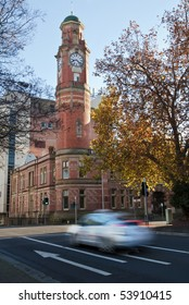 Blurred taxi at traffic lights near clock tower, Launceston, Tasmania, Australia. Early morning, Autumn scene.