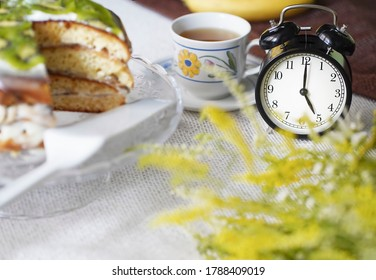 Blurred tea drinking composition.  Cup of tea, alarm clock showing 5 o'clock in the afternoon, homemade banana cake decorated with kiwi, wild flowersSummer concept.