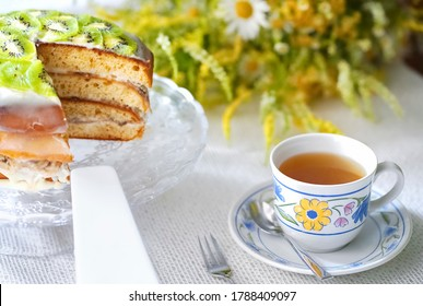 Blurred tea drinking composition.  Cup of tea, homemade banana cake decorated with kiwi, wild flowersSummer concept.