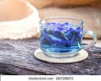 blurred tea juice butterfly pea in glass fresh purple or blue pea flower on wooden table. selective focus