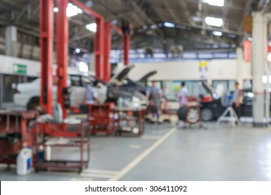 Blurred of technician repairing the car in garage background.