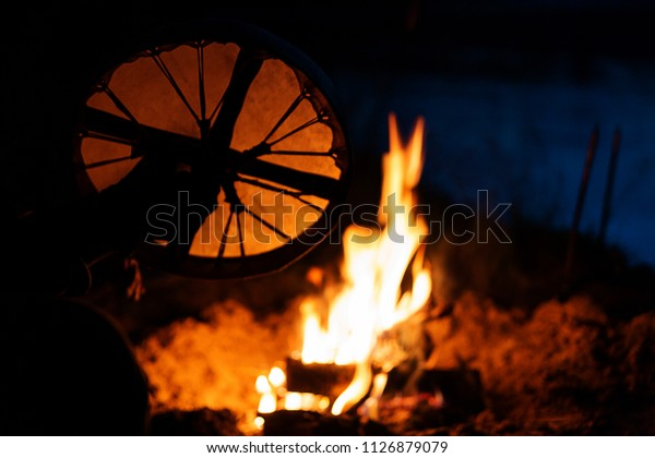 Blurred texture: a shamanic tambourine with a tambourine at the fire at night. Film grain and soft focus.