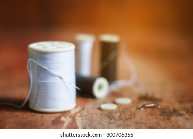 blurred of thread and needles on the old wooden background,vintage color tone.