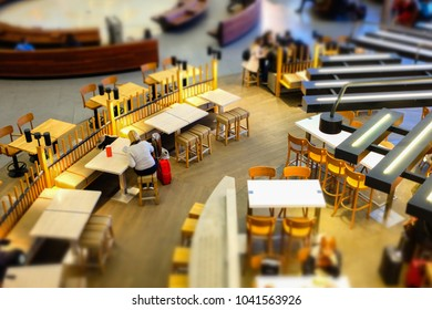 Blurred tilt-shift view of passenger in airport terminal. Interior background
