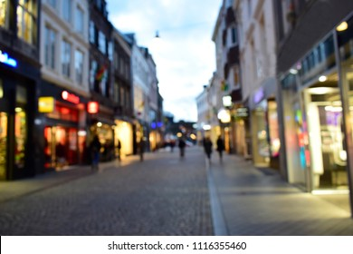 Blurred of tourist walking on sidewalk and enjoy shopping in street at night. Maastricht is one of the famous shopping center in Netherlands. Abstract background travel style and street view concept.