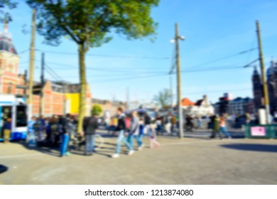 Blurred of tourists walking on the street in front of Amsterdam train station used for your background or your pattern design. Travel lifestyle and holiday concept.