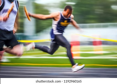 Blurred track and field runner crossing the finish line in a relay race