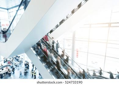 blurred traid fair crowd using a escalator